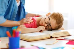 当她在家,做了她的家庭作业疲倦的儿童女孩睡着了 免版税库存照片