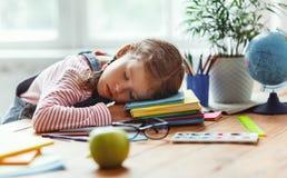 当她在家,做了她的家庭作业疲倦的儿童女孩睡着了 免版税库存图片