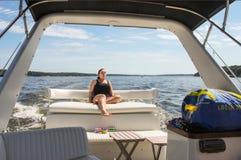 当她在游艇背后坐作为它横跨t,加速吸收太阳妇女在游泳衣享用在她的面孔的太阳 图库摄影