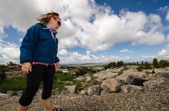 当她在蒙大拿,探索岩石和风景谨慎白肤金发的妇女观看她的立足处 免版税库存照片