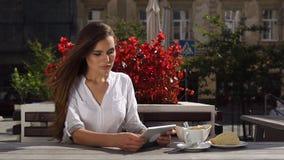 当她在餐馆坐在红色花前时,深色的夫人与片剂一起使用 影视素材