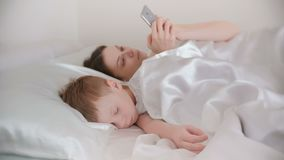 当她的儿子睡着时,妈妈醒了和她的手机的浏览互联网 股票录像