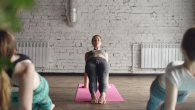 当她的学生重复时,女性瑜伽老师显示向上板条姿势Purvottanasana并且对此告诉 股票录像