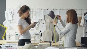 当她的工友与片剂一起使用时,专业裁缝测量在时装模特的样式与措施磁带 股票录像