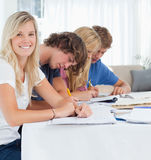 当她的朋友学习,一个微笑的女孩查看照相机 免版税库存照片