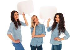 当她的朋友拿着讲话泡影时,妇女认为 免版税库存照片
