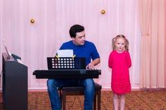 当她的父亲演奏合成器时,女孩唱歌 库存图片
