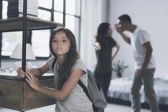 当她的父母在她后责骂她时,有一个背包的一个小深色头发的女孩在她后回顾去 库存照片