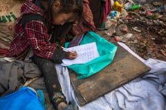 当她的父母在转储时,工作未认出的孩子坐 库存图片
