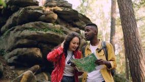 当她的男性朋友是时,有卷发的愉快的浅黑肤色的男人通过站立在森林里的双筒望远镜看在岩石附近 股票视频