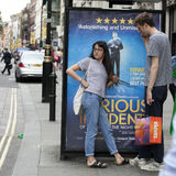 当她的男朋友将完成谈在电话,戴眼镜的女孩,穿戴在牛仔裤站立关于广告牌,等待 库存图片