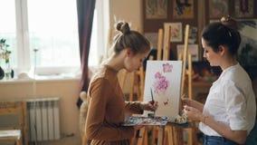 当她的老师悦目年轻女人给时,艺术学校的女生绘与油漆的花 股票录像
