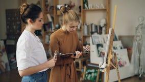 当她的老师老练的艺术家在她附近站立和时,少女学生在帆布绘使用油漆 股票视频