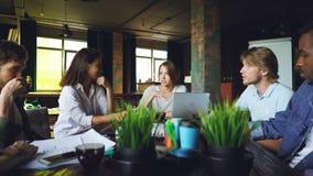 当她的队听着时,谈论的少妇与坐在桌上的同事讲话在办公室工作计划 股票录像