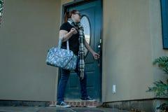 当她离开在家与一个行李袋一条胳膊,妇女锁她的前门 库存照片