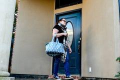 当她离开在家与一个行李袋一条胳膊,妇女锁她的前门 免版税库存图片