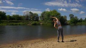 当她舒展准备跑,太阳突出年轻肌肉女运动员 股票录像