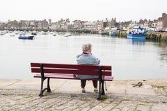 当她观看看法在沿海岸区和小船,一名年长资深妇女坐长凳 资深人概念的寂寞 库存照片