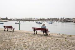 当她观看看法在沿海岸区和小船,一名年长资深妇女坐长凳 资深人概念的寂寞 免版税图库摄影