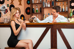 当她谈话,英俊的男服务员倾吐一杯酒精在女孩 免版税库存图片