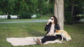 当她逗人喜爱的狗嗅到地面时,轻松的女孩是阅读书和饮用的外带的咖啡坐草坪在公园 股票录像
