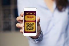 当妇女拿着它时,在一个手机的戏院票筛选 图库摄影