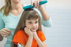 当妈妈梳她的头发时,一个美丽的女儿看起来逗人喜爱在镜子 库存照片