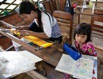 当孩子做家庭作业时,母亲工作织布机 图库摄影