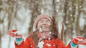 当它落时,一位年轻女小学生快乐投掷雪球并且打破它与棕榈 喜悦的情感 冬天乐趣 免版税库存图片