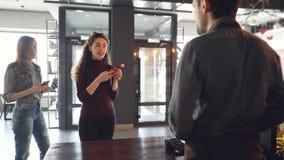 当客户队列是等待和使用手机时,咖啡馆的快乐的顾客付与智能手机的付款 股票视频
