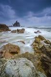 当小时挥动击中石头在海滩以剧烈的黑暗在风暴前覆盖背景 免版税库存照片