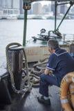 当小船在香港,横渡维多利亚港口星轮渡职员坐 免版税库存照片