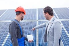 当工作者站立与在太阳电池板时,背景的一个笔记本院长指向太阳能电池 免版税库存图片