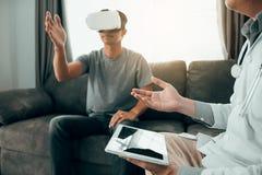 当患者佩带,医生使用片剂送数据到显示健康诊断的虚拟现实玻璃 库存照片