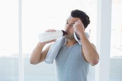 当抹冒汗了与毛巾在健身演播室时,供以人员饮用水 库存照片