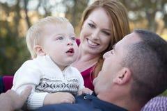 当新父项微笑,逗人喜爱的子项查寻对天空 图库摄影