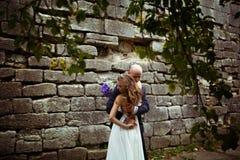 当新郎拥抱她在树下时,风吹去新娘的头发 免版税库存图片