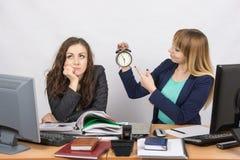 当晚工作的办工室职员,一个与微笑,表明时钟,其他周道地扶植头 库存图片