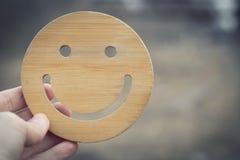 当有干净和生态时,有心情 手拿着在被弄脏的自然背景的木圆的smilie 免版税图库摄影