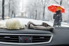 当有红色伞的夫人走时,概念冬天射击了在一辆汽车的童帽在前窗后 免版税库存照片