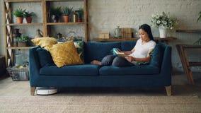 当机器人吸尘器是干洗地板时,美丽的亚裔女孩是基于沙发的阅读书在客厅 股票视频