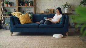 当机器人真空吸尘器清洗地板做时,轻松的亚裔妇女是阅读书转动的页在家坐长沙发 影视素材