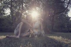 当母亲拿着他们的toddl时,在公园结合坐在草 库存照片