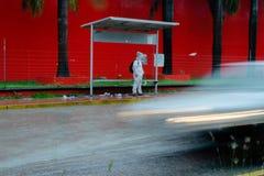 当汽车驾驶通过他时,人在雨中站立在公交车站 免版税库存图片