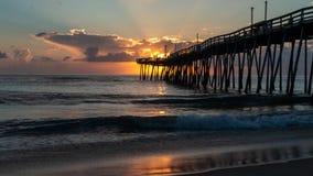 当渔夫熔铸他们的从一个老木码头的末端的线在日出,剧烈的天窗与黄光的云彩 免版税库存图片