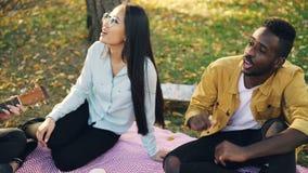 当漂亮的女人是使用时,快乐的朋友不同种族的小组在公园唱歌曲坐毯子 股票视频