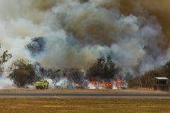 当灌丛火关闭圣萨尔瓦多国际机场,消防员浪花发火焰 免版税库存图片