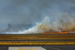 当灌丛火关闭圣萨尔瓦多国际机场,消防车动员 免版税库存照片
