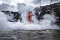 当热的熔岩涌入水,蒸汽从冷的海洋喷发 库存照片