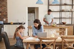 当父亲做膳食,母亲帮助有家庭作业的女儿 免版税库存照片